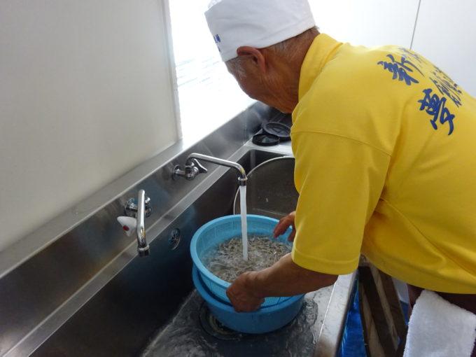 茹であがったそばを洗う