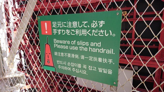 「足元に注意して必ず手すりをご利用ください。」の看板。