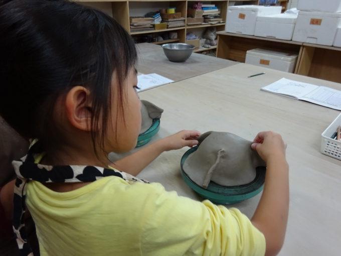 手ろくろに乗せて、今度は丸くなった粘土を茶碗にするため余分な部分をつまみます。