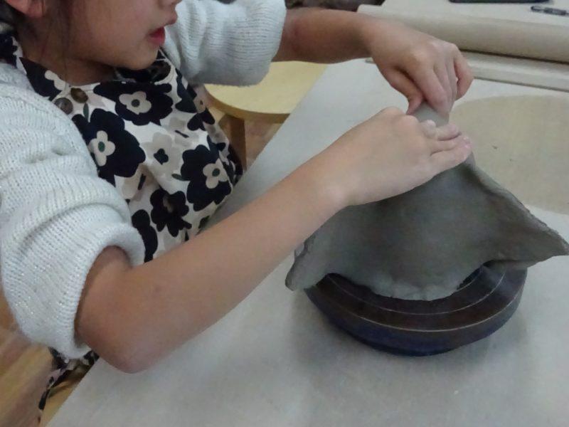 手ろくろに乗せて、丸くなった粘土をマグカップにするため余分な部分をつまみます。