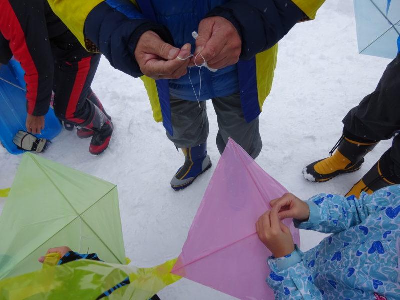 連凧が揚がる前に、凧揚げ工房の方が、配布した凧に紐をつけてくれます。