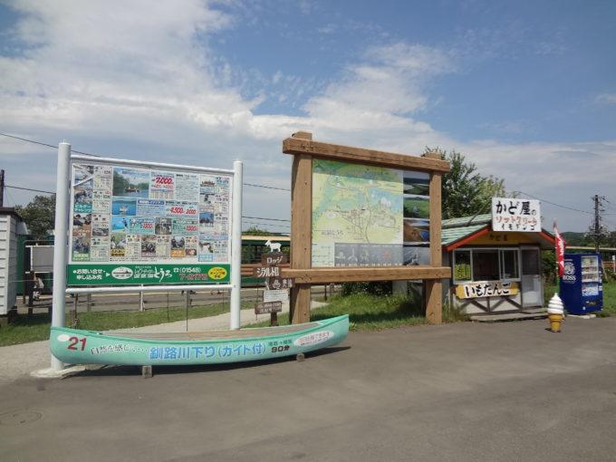 塘路駅の改札を出ると、塘路駅周辺の案内看板とレイクサイド塘路の体験案内看板、そして大きなカヌー