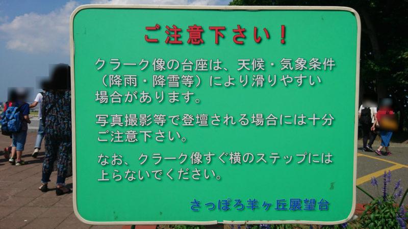 「クラーク像の台座は、天候・気象条件(降雨・降雪)により滑りやすい場合があります。」の注意看板。