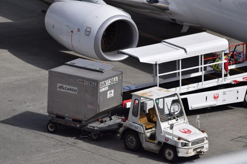 貨物や手荷物が入ったコンテナを運ぶJALのタグ車