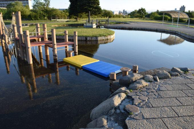 遊水路に浮かぶ青と黄のマット