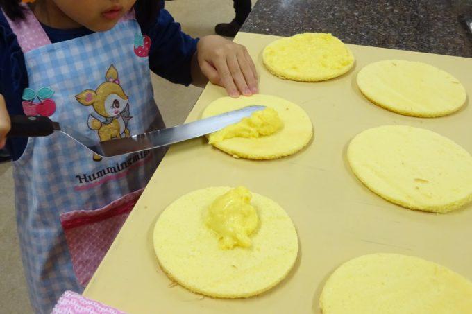 スパチュラを使ってカスタードクリームを生地に塗ります。