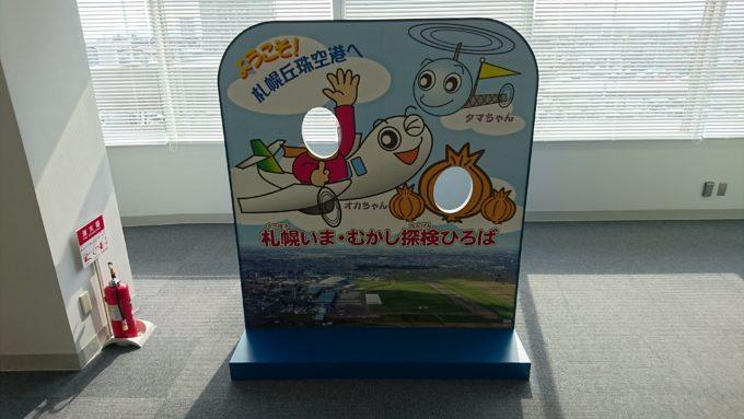 札幌いま・むかし探検ひろばにある札幌丘珠空港「オカちゃん・タマちゃん」の顔ハメ看板