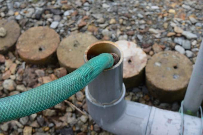 温泉水が出る緑のホースが灰色のパイプに入っています