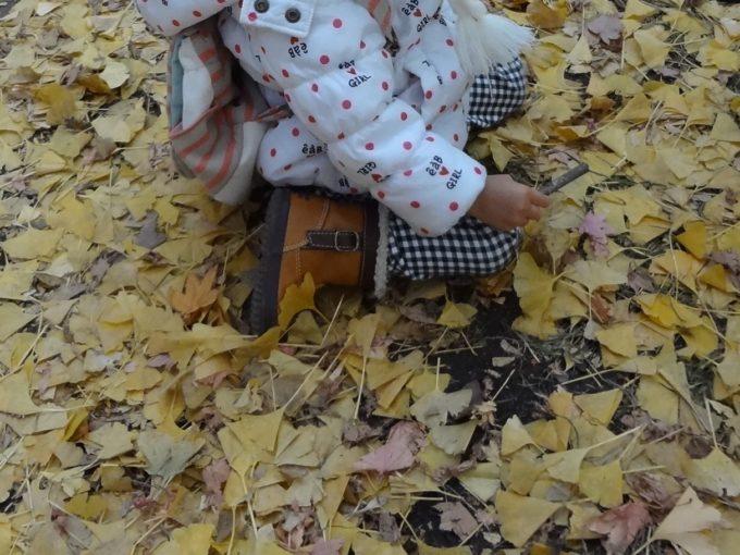 イチョウの落ち葉で遊ぶ子供